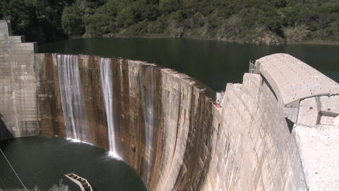 Pan side view of water spilling over the Matilija Dam in Ojai, California Footage