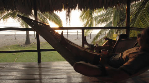 Time lapse of man sitting in a hammock in palapa at La Saladita Beach, Guerrero, Mexico Footage