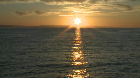 Pan of the sun setting over the Channel Islands and the Pacific Ocean at Ventura, California Footage