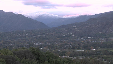 Slow pan of sunrise on the snow-covered Santa Ynez Mountains above Ojai, California Footage