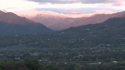 Wide zoom out of sunrise on the snow-covered Santa Ynez Mountains above Ojai, California Footage
