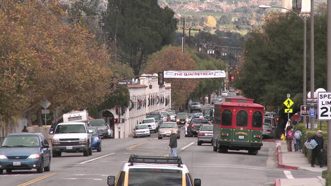 Zoom out of cars driving and people crossing the street in downtown Ojai, California Footage