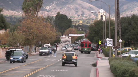 Zoom out of cars driving and people crossing the street... Stock Video Footage