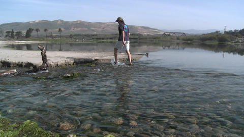 Panning of a man walking in the water in the Ventura River Estuary at Surfers Point in Ventura, Cali Footage
