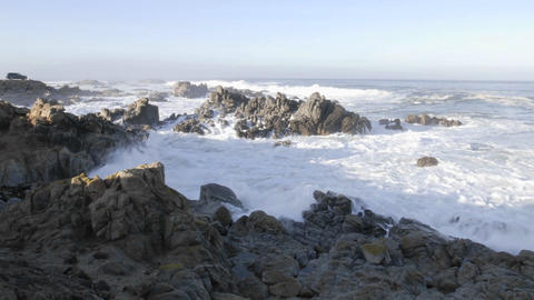 Wide panning time lapse of waves breaking on the rocks at... Stock Video Footage