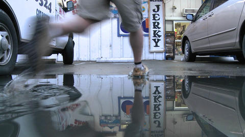 Man jumping over water puddle at a store in Ojai, California Stock Video Footage