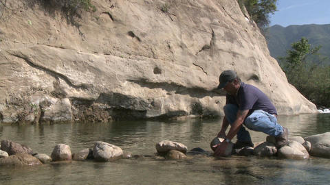 Man removing rocks from a fish barrier on the Ventura... Stock Video Footage