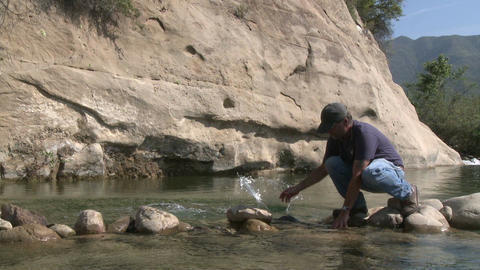 Man removing rocks from a fish barrier on the Ventura River Preserve in Ojai, California Footage