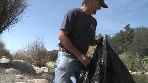 Man picking up trash on the Ventura River Preserve in Ojai, California Footage