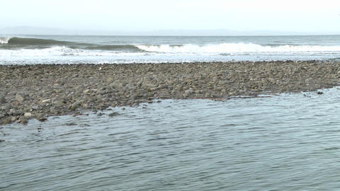 Tilt up of water flowing out of the Ventura River estuary and waves at Surfers Point in Ventura, Cal Footage