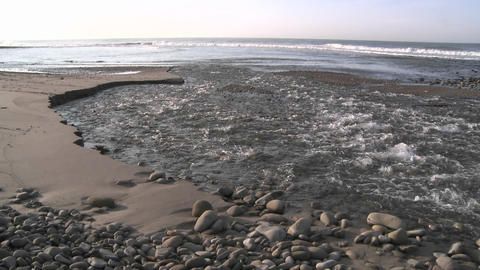 Water flowing out of the Ventura River estuary at Surfers... Stock Video Footage