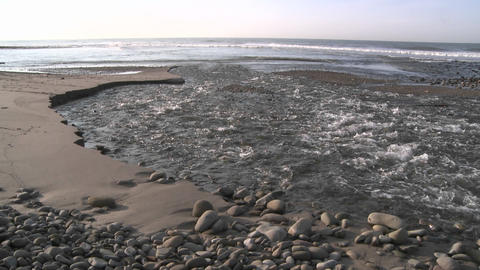Water flowing out of the Ventura River estuary at Surfers Point in Ventura, California Footage