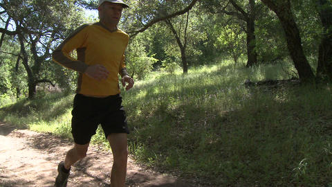 Pan of a man trail running in the forest on the Ventura River Preserve in Ojai, California Footage