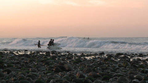 Surfers paddling out at into the waves at Surfers Point in Ventura, California Footage