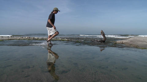 Panning of man walking through the water in Ventura River Estuary at Surfers Point in Ventura, Calif Footage