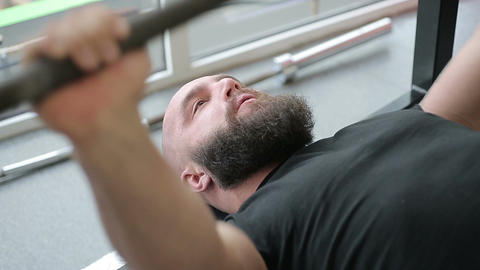 Strong heavyweight athlete thoroughly doing barbell exercise with strained face Live Action