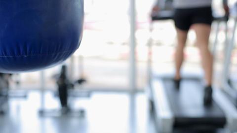 Defocused man walking on treadmill, punching bag hanging in gym, background shot Footage