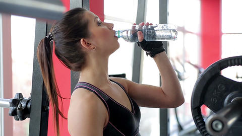 Beautiful girl drinking clear water after active sports workout at fitness club Footage