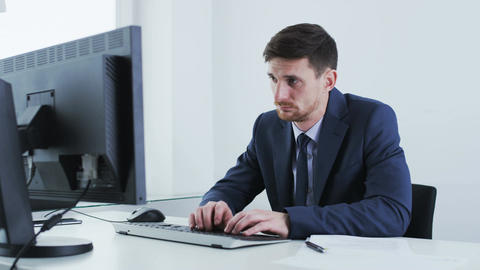 Young businessman yawns while looking at a stationary computer Footage