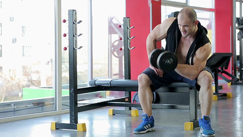Male bodybuilder doing dumbbell exercises with strained face, active workout Live Action