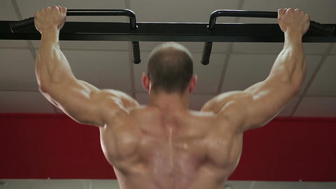 Bodybuilder with perfect muscular body doing pull-ups, preparing for competition Footage