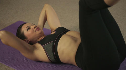 Female athlete doing crunches with legs up, exercises for beautiful fit body Footage