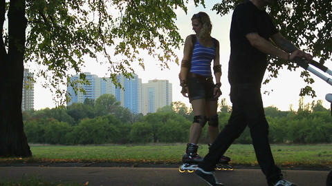 Father walking with baby in stroller, mother and daughter enjoy rollerblading Footage