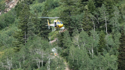 Rescue helicopter lifts load from high mountain HD 8638 Footage