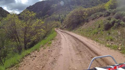 Riding ATV muddy mountain road sun flare POV HD Footage