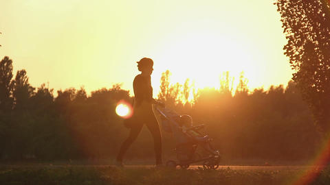 Young woman talking on phone while walking with baby in stroller, magic hour Footage