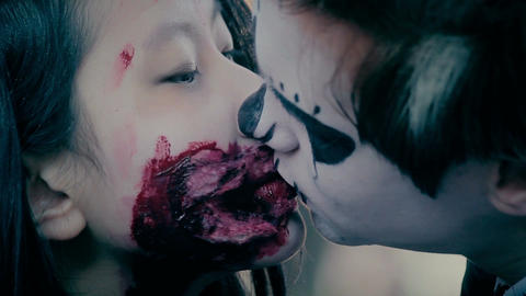 Male and female teenagers with scary makeup on faces kissing at Halloween party Live Action