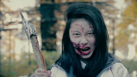 Crazy female zombie murderer with bloody axe looking aggressively into camera Footage