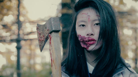 Furious female monster with bloody wound on face, murderer threatening with axe Live Action