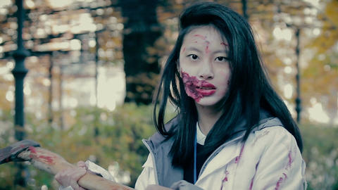 Actress with scary makeup on face chopping at camera with sharp axe, horror film Live Action