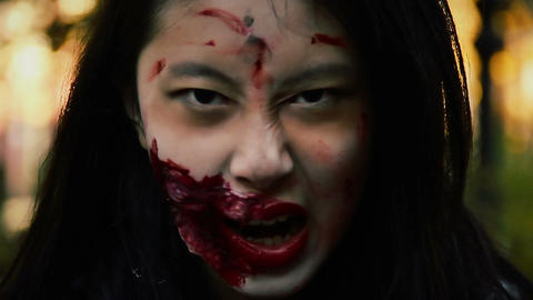 Dangerous female vampire with bloody injury on face looking fiercely at victim Live Action