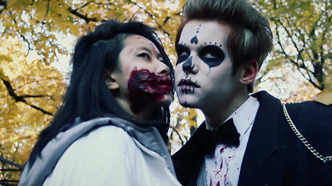Young couple kissing at Halloween party, man and woman in zombie suits have fun Live Action