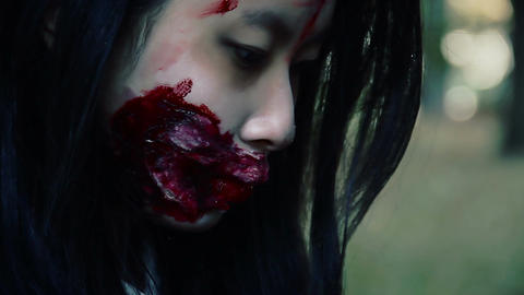 Closeup of bloody female face, injured woman looking down, victim of accident Live Action