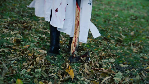 Serial maniac in white coat dragging bloody murder weapon from crime scene Live Action