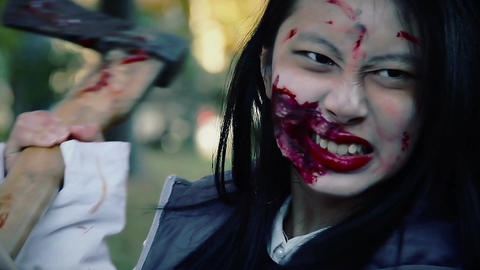 Actress playing role of crazy murderer, chopping with bloody axe at victim Live Action