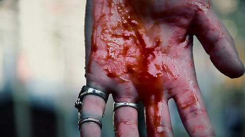 Suicidal man cutting veins, blood running down person's hand, clenching fist Footage