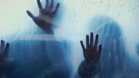 Souls of dead people smearing blood on transparent surface, scary horror film Live Action
