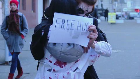 Young people enjoying Halloween flash mob, having fun with free hugs sign Footage