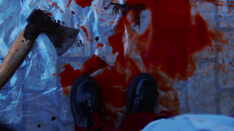 Maniac dropping murder weapon in pool of blood on ground, corpse dissection Live Action