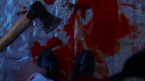 Crazy murderer dropping axe in pool of blood, leaving crime scene, horror film Live Action
