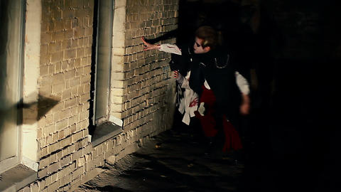 Two scary zombies wandering in darkness, hiding from lights, haunted building Live Action