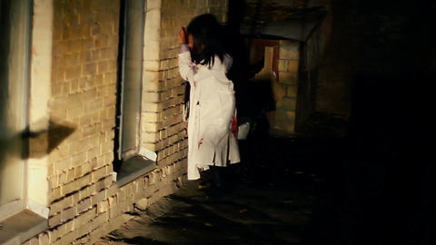 Strange female in ragged bloody clothes limping in dangerous dark street Live Action