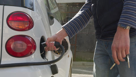 Man's hand inserts the charging cable to charge the electric car. Charging an Live Action