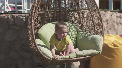 Entertaining boy swaying in a cane swing in summer in slo-mo Live Action