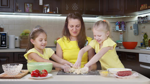 Mom and children cook pizza in the kitchen. Children help their mother to cook Live Action