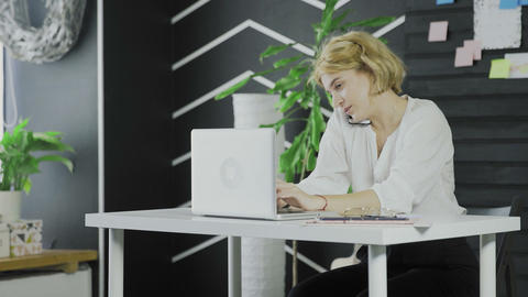 Attractive business woman talking on the cell phone while typing on laptop Live Action